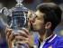 Novak Djokovic besa el trofeo de campeón del Abierto de Estados Unidos tras vencer a Roger Federer en la final, el domingo 13 de septiembre de 2015. (AP Foto/Julio Cortez).