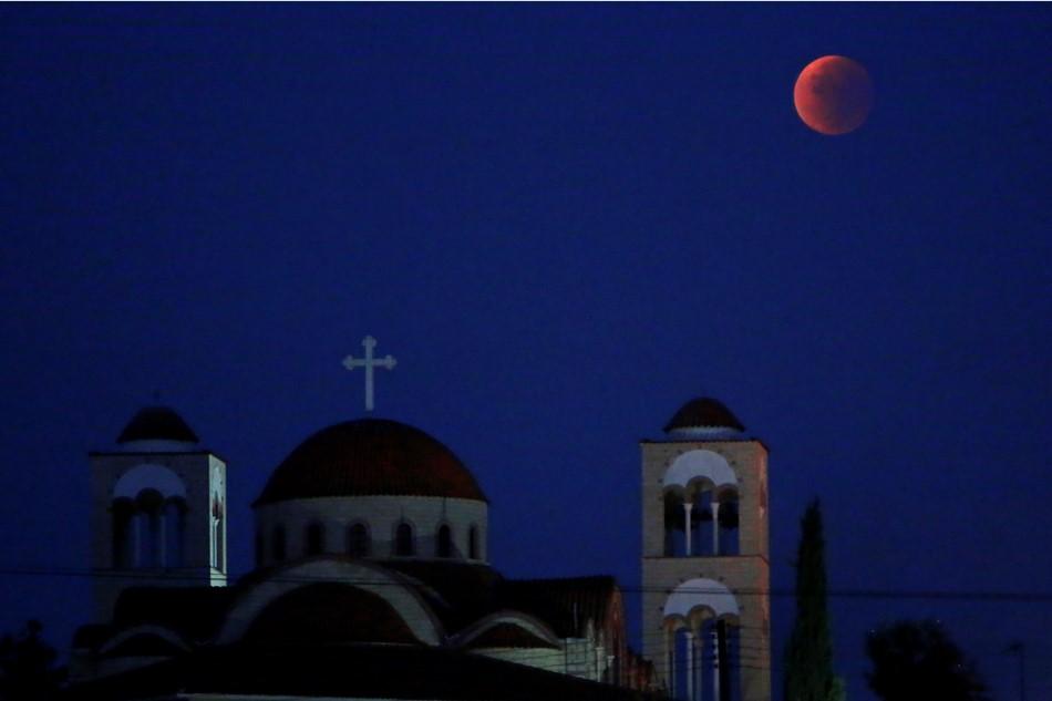 """La """"Luna de sangre"""" brilla sobre una iglesia cristiana ortodoxa en Anthoupolis, un suburbio de Nicosia, en Chipre, en la madrugada del lunes 28 de septiembre de 2015. (AP Foto/Petros Karadjias)"""