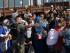Amina Asmani, segunda de derecha a izquierda, observa a un policía que vigila las vías antes de que un tren que llevará a inmigrantes a Serbia llegue a la estación en el pueblo del sur de  Macedonia de Gevgelija. El paso de miles de inmigrantes de Siria, Irak, Afganistán y otros países ha sido registrado por este empobrecido país de los Balcanes en el último mes, la cantidad es del doble que un mes anterior. (Foto AP/Darko Vojinovic)