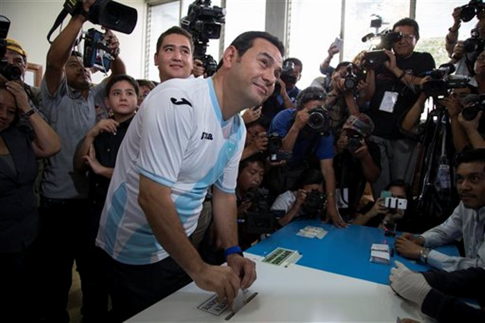 El candidato presidencial Jimmy Morales, con la camiseta de la selección guatemalteca de fútbol, votar en la segunda ronda presidencial en un local de sufragio en Mixco, Guatemala, el domingo 25 de octubre de 2015. Morales se enfrenta a la ex primera dama Sandra Torres. (AP Photo/Luis Soto)