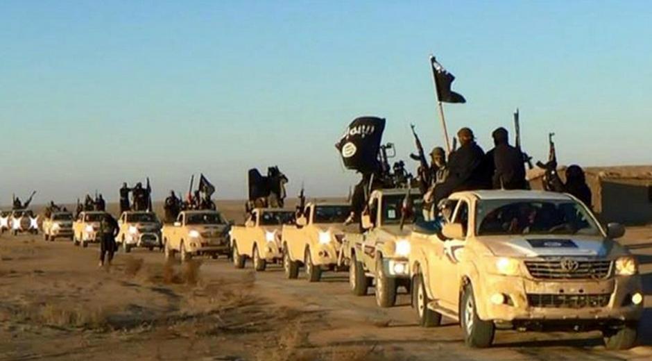 En esta imagen sin fecha difundida por un sitio web miliciano, que ha sido verificado y coincide con otra información de AP, milicianos del grupo Estado Islámico sostienen sus armas y ondean banderas en un convoy con varios vehículos a través de la ciudad de Raqa, en Siria.. (Sitio miliciano via AP, Archivo)