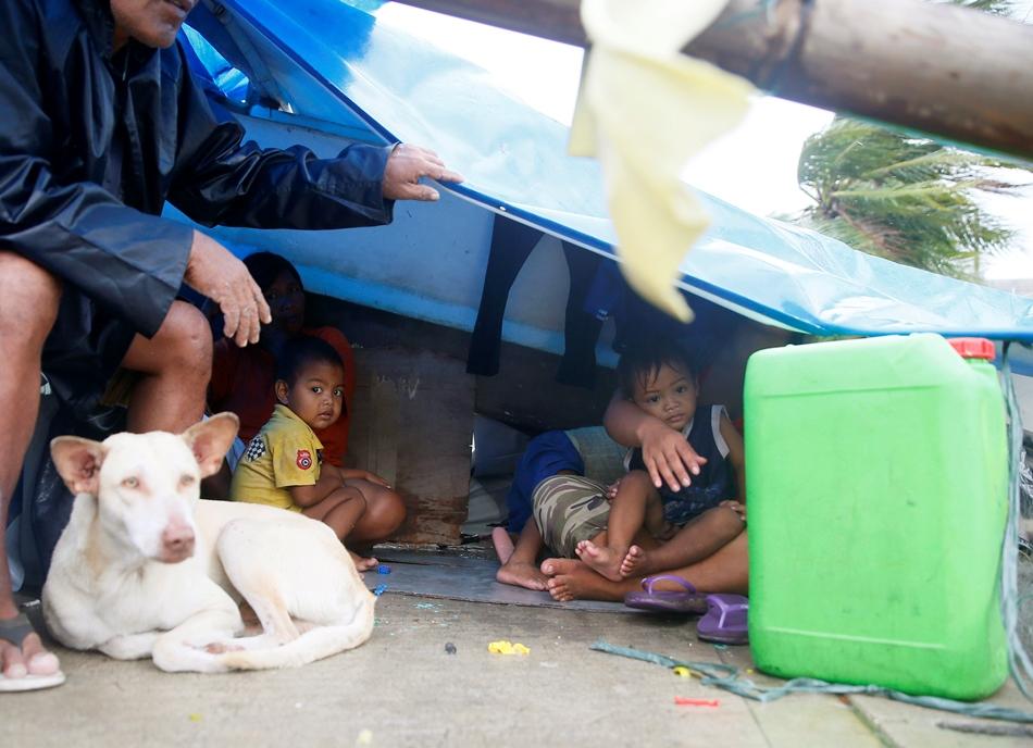 Una familia se refugia bajo un plástico junto a una pared de concreto de los fuertes vientos y lluvias provocados por el tifón Koppu, el 18 de octubre de 2015 en Manila, Filipinas. (Foto AP/Bullit Marquez)