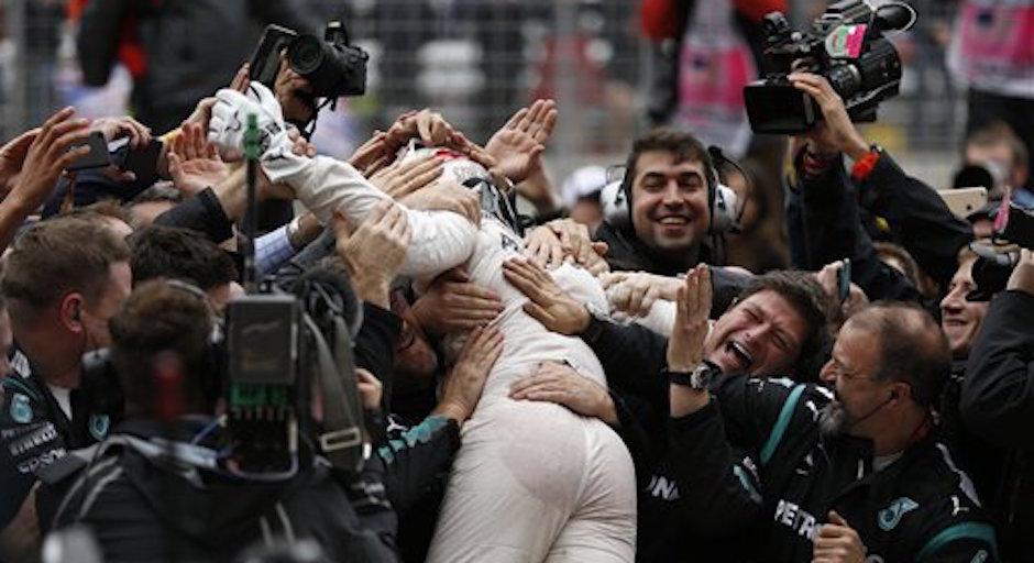 Lewis Hamilton recibe la felicitaciÛn de los integrantes de su equipo Mercedes tras ganar el GP de EEUU y el tÌtulo del mundial de FÛrmula Uno, en Austin, Texas, el domingo 25 de octubre de 2015. (AP Foto/John Locher)