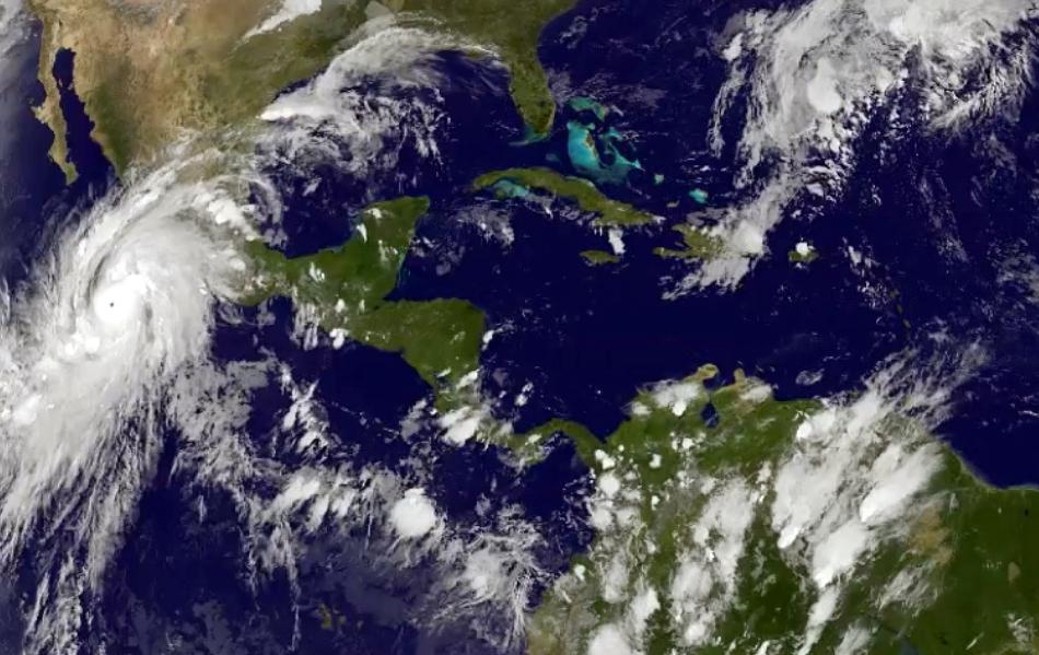 Esta imagen satelital tomada a las 8:45 p.m. hora del Este el jueves 22 de octubre de 2015, y dada a conocer por laOficina Nacional de Administración Oceánica y Atmosférica, muestra al huracán Patricia, a la izquierda, moviéndose hacia costas centrales del Pacífico mexicano. (NOAA via AP)