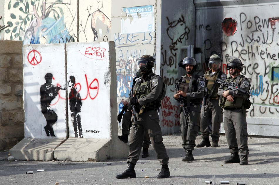 Policías fronterizos israelís frente a la Ribera Occidental en un punto de revisión entre Jerusalén y Belén durante los enfrentamientos con manifestantes palestinos el viernes 2 de octubre de 2015. El ejército de Israel desplegó a cientos de tropas el viernes en la Ribera Occidental, luego de que un atacante disparó desde un auto en movimiento, matando a una pareja judía que se dirigía a casa con sus hijos. (Foto AP/Mahmoud Illean)