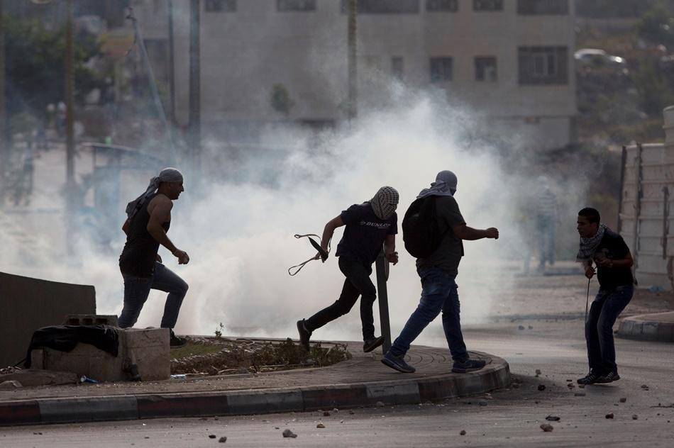 Palestinos se desplazan rápidamente entre nubes de gas lacrimógeno durante enfrentamientos con las fuerzas israelíes cerca de Ramala, en Cisjordania, el lunes 12 de octubre de 2015. Israel y Cisjordania han sido escenario en los últimos días de varios ataques con cuchillos en los que fueron heridos varios israelíes. (AP Foto/Majdi Mohammed)