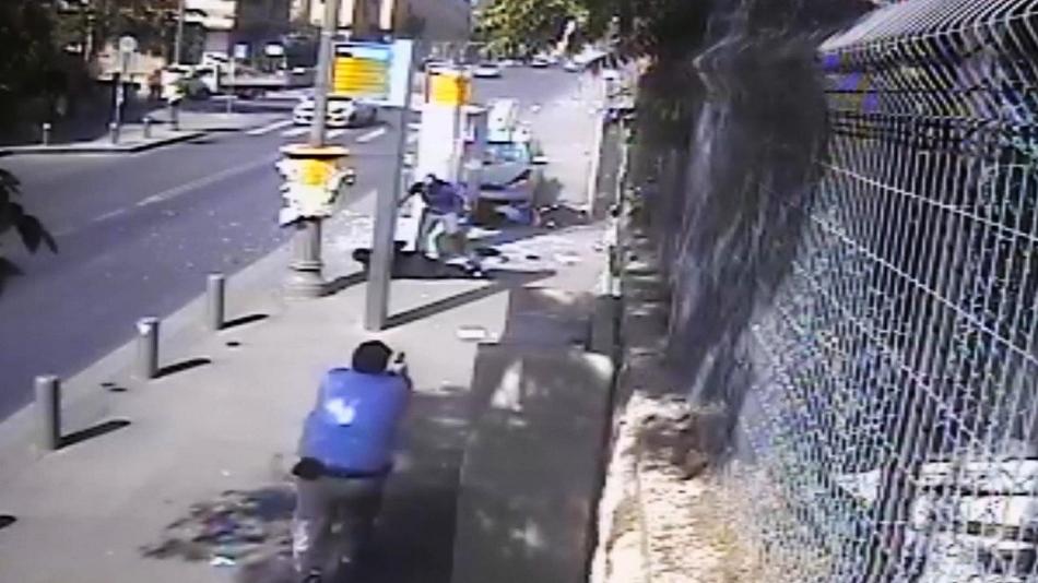 En esta imagen, tomada de un video de una cámara de seguridad proporcionado por la policía de Israel, muestra a un hombre (en el centro con camisa azul) atacando a una persona tras haber estrellado su auto contra una parada de autobús (detrás), mientras un guardia de seguridad civil con una pistola en la mano se acerca al atacante, en Jerusalén, el 13 de octubre de 2015. (Israel police via AP)