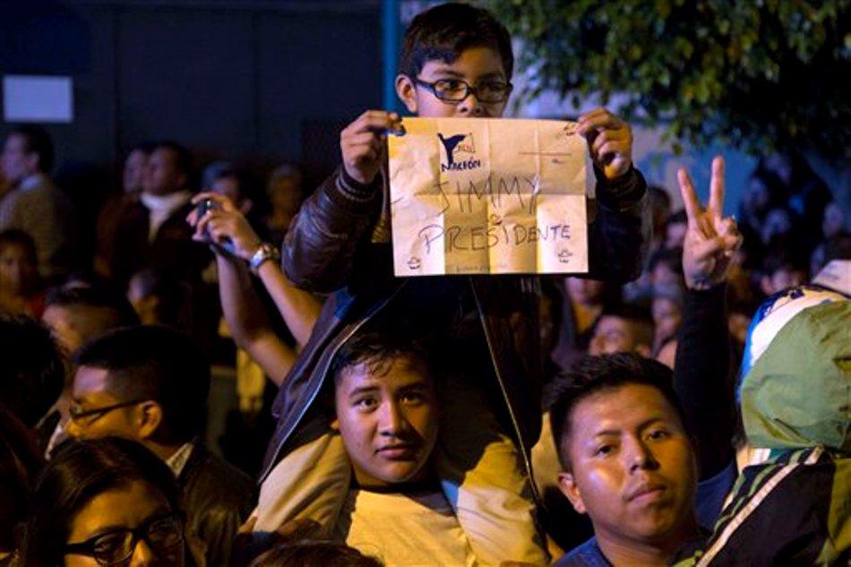 """Un niño sostiene un cartel en el que ouede leerse """"Jimmy presidente"""" mientras partidarios del Frente de Convergencia Nacional esperan a su candidato, en la ciudad de Guatemala, el 25 de octubre de 2015. Morales, un cómico de televisión, reclamó la victoria y su oponente, la ex primera dama Sandra Torres, reconoció la derrota luego de que resultados oficiales diesen la victoria a Morales con un 69% de los votos con el 94% del conteo electoral completado. (Foto AP/Luis Soto)"""