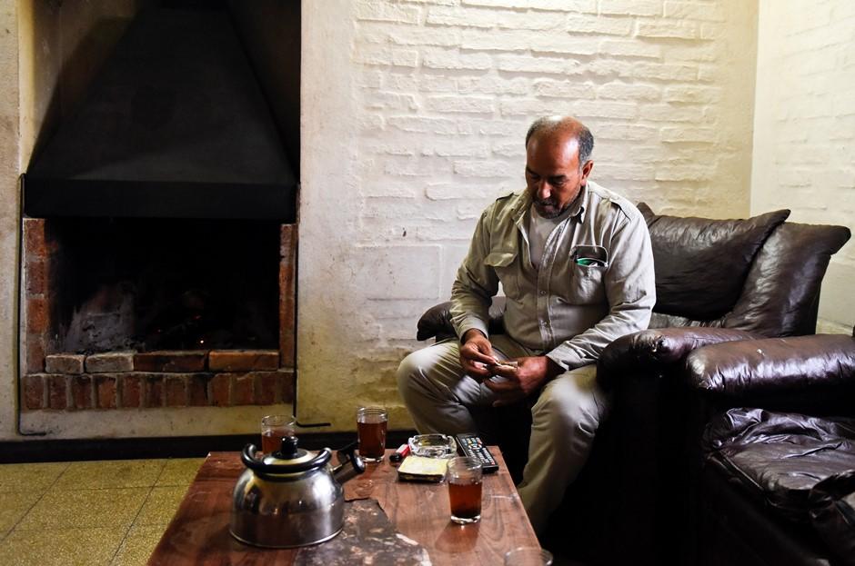 En esta fotografía del 7 de octubre de 2015 Merhi Alshebli saca un cigarrillo en la sala de estar de su casa en Juan Lacaze, Uruguay. En noviembre de 2014 los locales dieron la bienvenida a Alshebli, su esposa y sus 15 hijos que huían de la guerra civil en Siria. Pero después de meses de quejas sobre sus condiciones de vida en Uruguay y las demandas de que los envíen a otro país, muchos en esta ciudad han empezado a ver a los refugiados como huéspedes ingratos. (AP Foto/Matilde Campodonico )