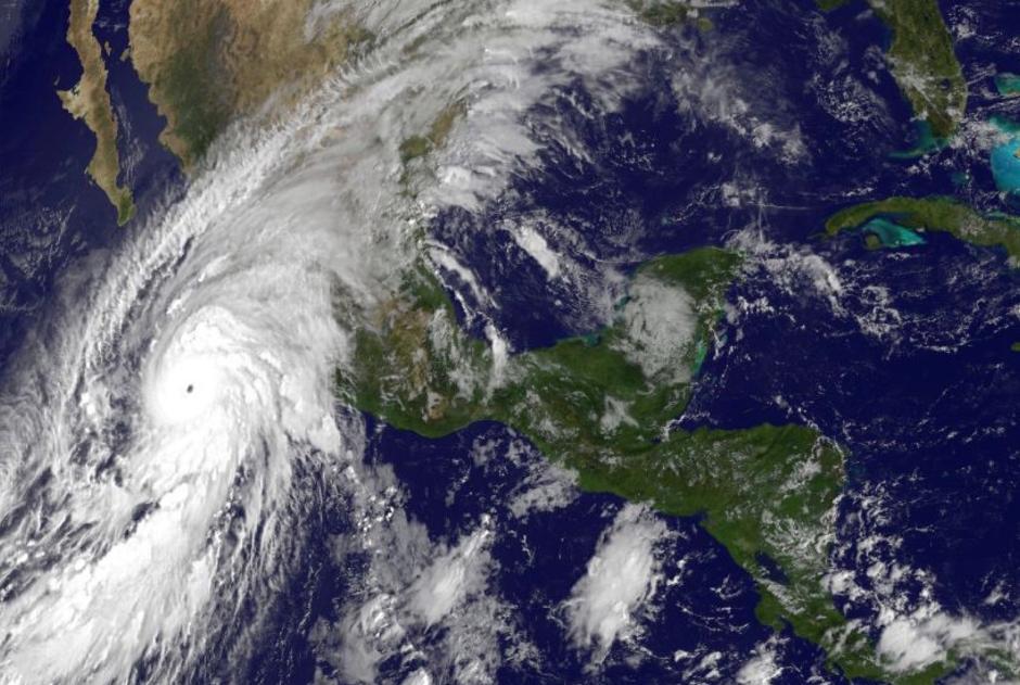 La imagen satelital tomada a las 11:00 de la mañana el viernes 23 de octubre de 2015, y dada a conocer por la Oficina Nacional de Administración Oceánica y Atmosférica de Estados Unidos muestra al huracán Patricia, izquierda, dirigiéndose a la costa mexicana en el Pacífico. (NOAA vía AP)