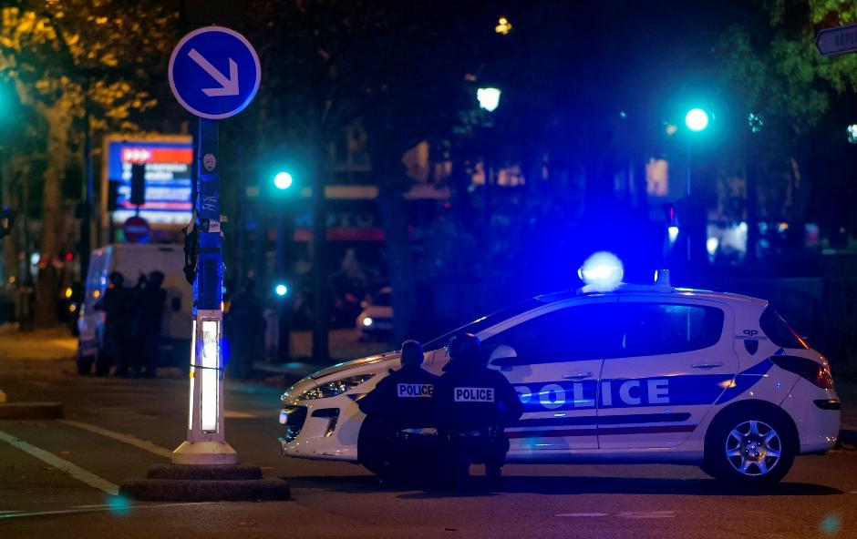 Agentes de la policía se cubren detrás de vehículos afuera del teatro Bataclan en París, Francia, el viernes 13 de noviembre de 2015. (AP Foto/Kamil Zihnioglu)
