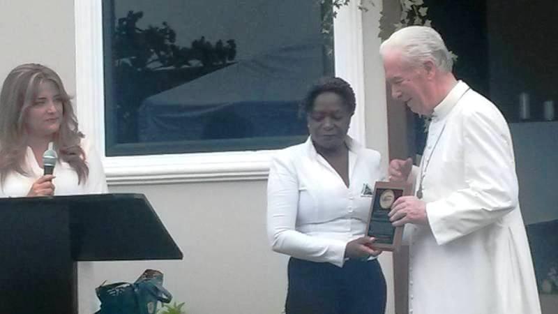 Representante de Fundación Montessori entregando placa a Mons. Arregui.