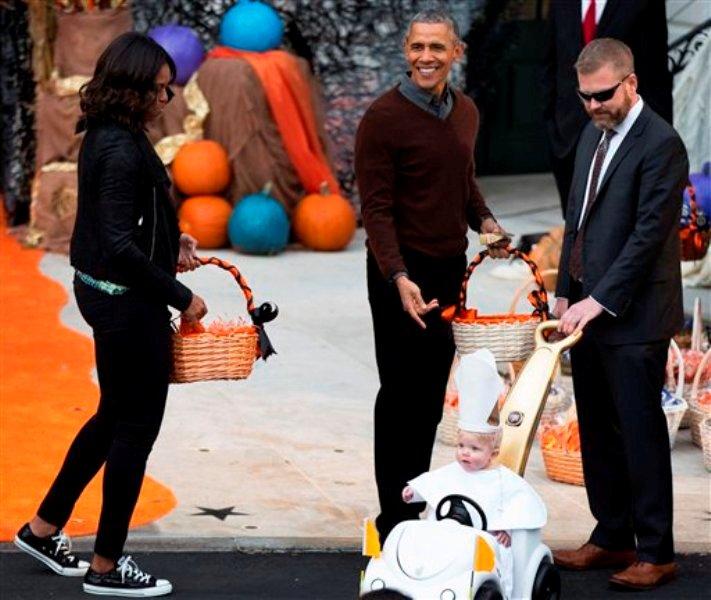 El presidente Barack Obama y la primera dama Michelle Obama, a la izquierda, saludan a un niño vestido de pontífice en su papamóvil durante la fiesta de Halloween que se efectuó en el Jardín Sur de la Casa Blanca en Washington, el viernes 30 de octubre de 2015. A la celebración asistieron niños locales y de familias del ejército. (AP Foto/Andrew Harnik)