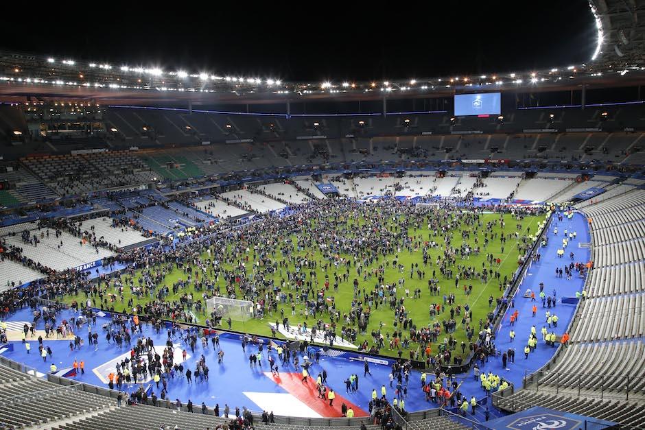 Los espectadores invaden la cancha del Stade de France tras el encuentro amistoso entre las selecciones de Francia y Alemania el viernes 13 de noviembre de 2015 en Saint Denis, en las afueras de París. Al menos dos decenas personas han muerto en tiroteos y explosiones en diversas partes de París, informaron dos oficiales de policía, en los hechos de violencia más letales en Francia en décadas. (Foto/Michel Euler)
