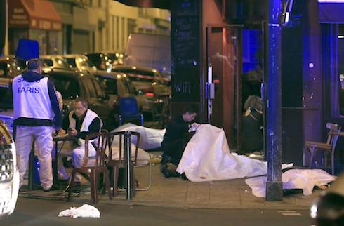 Varias víctimas yacen en el piso afuera de un restaurante de París el viernes 13 de noviembre de 2015. La policía informó de diversos hechos de violencia en la capital francesa. (Foto AP/Thibault Camus)