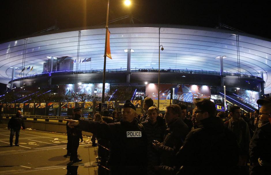 Un policía dirige a la gente afuera del estadio Stade de France durante el partido amistoso de Francia contra Alemania, el viernes 13 de noviembre de 2015 en Saint Denis, en las afueras de París. Al menos dos explosiones se escucharon cerca del estdio, y los medios franceses reportaron que hay una toma de rehenes en la capital. (Foto AP/Michel Euler)