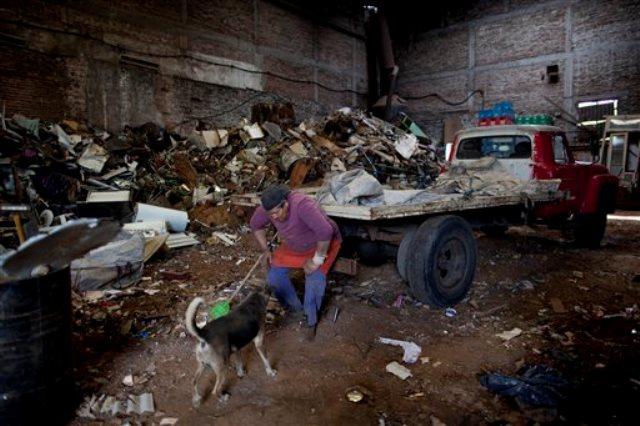En esta imagen de archivo del 2 de noviembre de 2015, Marcelo Monzon mira a un perro dentro del centro de reciclaje donde trabaja en Buenos Aires, Argentina.  (AP Foto/Natacha Pisarenko)