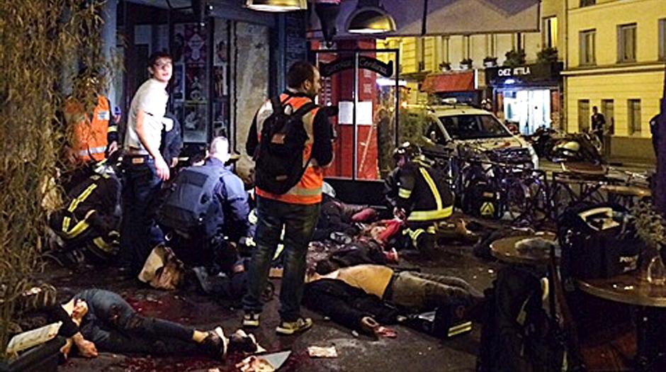 Víctimas de un ataque a tiros yacen en el suelo afuera del restaurante La Belle Equipe en París, el viernes 13 de noviembre de 2015. Más de 100 personas perdieron la vida el viernes en la noche en una oleada de ataques a tiros y explosiones en diversos lugares en París, según las autoridades. (Vía AP Foto/Anne Sophie Chaisemartin)