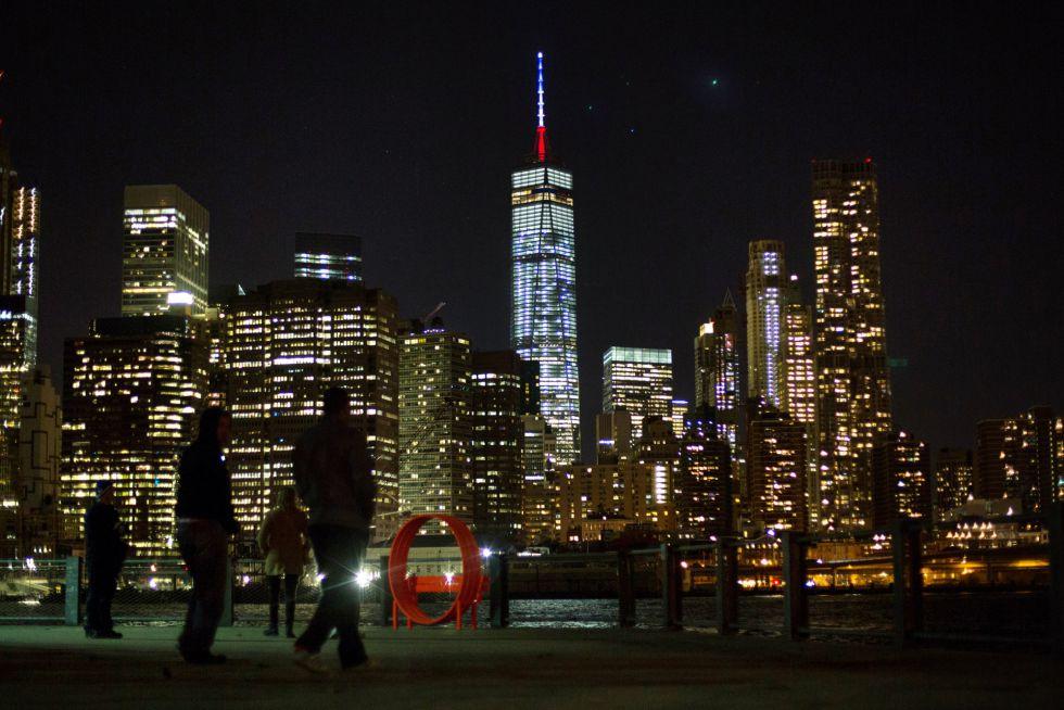 Unos viandantes observan desde la distancia The One World Trade Center, el edificio más alto de la zona este de Nueva York (EE UU), iluminado con los colores de Francia en solidaridad con las víctimas de los atentados perpetrados. KEVIN HAGEN (AP)