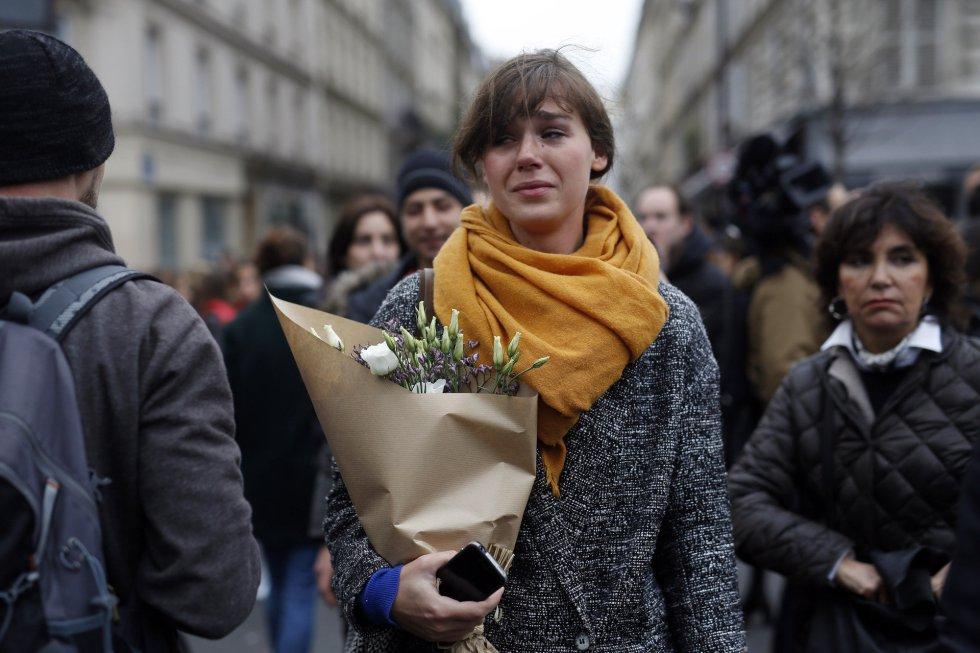 Una joven lleva un ramo de flores para rendir homenaje a las víctimas en la zona de Le Carillon y Le Petit Cambodge. JEROME DELAY (AP)