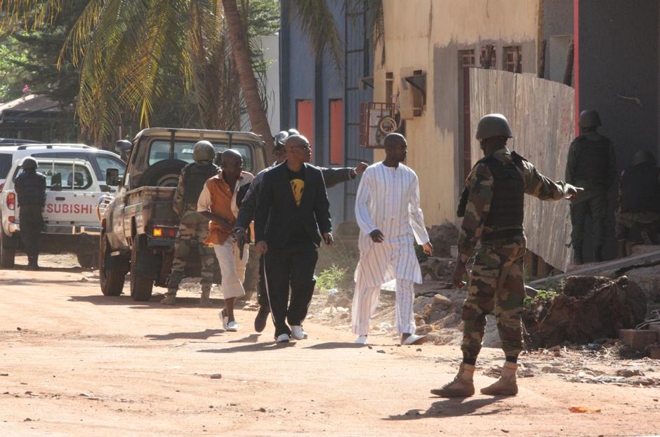 En la imagen, personal de seguridad escolta a personas que huyen del hotel Radisson Blu en Bamako, Mali, el viernes 20 de noviembre de 2015, donde varias personas lanzaron un ataque y tomaron rehenes. (AP Foto/Harouna Traore)