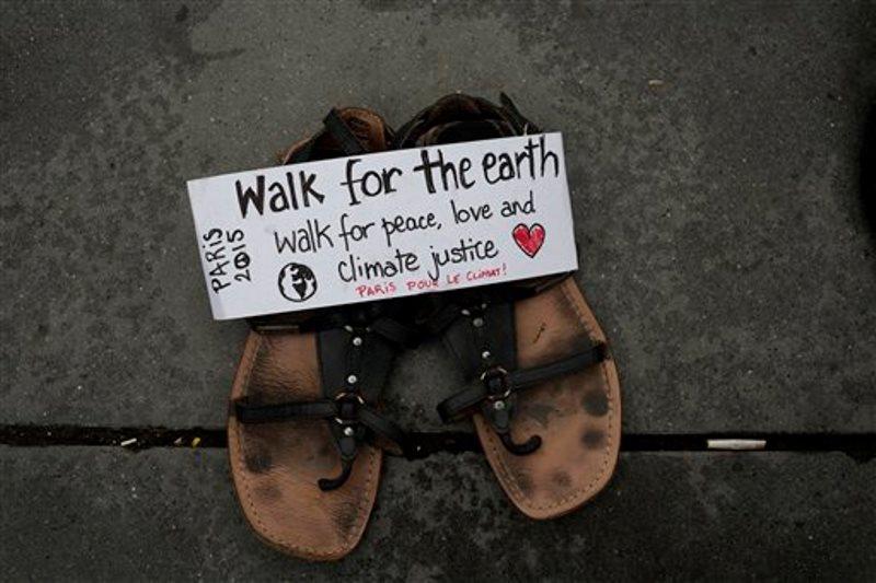 """Un mensaje que dice """"Marcha por la tierra"""" está colocado sobre un par de sandalias colocadas entre cientos de zapatos en la Plaza de la Republica en París, el domingo 29 de noviembre de 2015, como parte de una marcha simbólica. Activistas medioambientales, entre otros, depositaron el domingo zapatos en las calles de París para pedir a los más de 140 líderes mundiales que participarán el lunes en el inicio de la Cumbre del Clima que alcancen un pacto que ralentice el calentamiento global. Una gran marcha organizada por activistas para el domingo fue prohibida por el estado de emergencia impuesto en Francia tras los ataques del 13 de noviembre. (Foto AP/Laurent Cipriani)"""