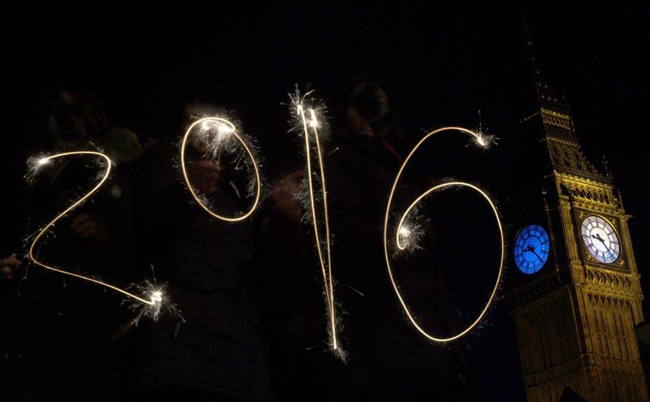 Fotografía de larga exposición en la que varias personas escriben el número 2016 hoy, jueves 31 de diciembre de 2015, frente a la Torre de la Reina Isabel y la Casa del Parlamento, en Londres (Reino Unido). Cerca de 100.000 personas se espera que participen en las festividades de Año Nuevo alrededor del Río Támesis. EFE/Hannah Mckay