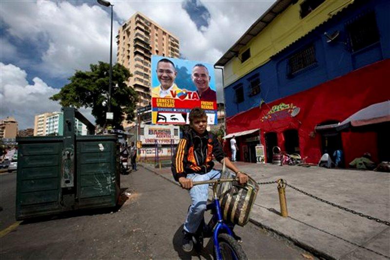 Un niño pasa en bicicleta frente a un cartel de candidatos oficialistas a las elecciones legislativas en Caracas, Venezuela, 4 de diciembre de 2015.  Los venezolanos se aprestan a votar en elecciones legislativas el 6 de diciembre, donde las encuestas dan 30 puntos de ventaja a la coalición opositora. La delincuencia, la alta inflación y la carencia de productos básicos han debilitado al gobierno bolivariano, que enfrenta la posibilidad de su primera derrota grave en 17 años.  (AP Photo/Fernando Llano)
