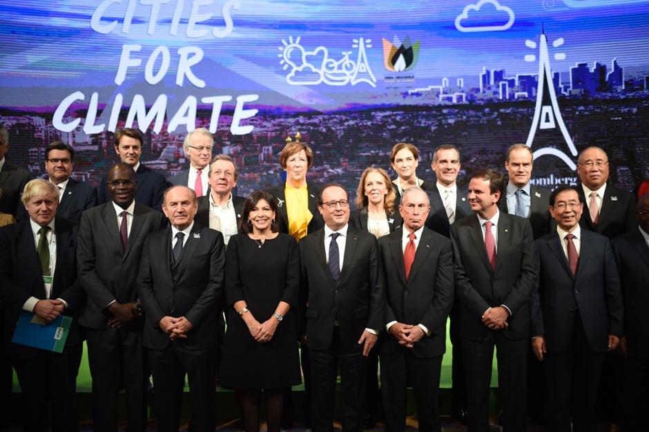 El presidente de Francia, François Hollande (centro) posa con la alcaldesa de París, Anne Hidalgo (centro izquierda); el alcalde de Londres, Boris Johnson (izquierda); el ex regidor de Nueva York, Michael Bloomberg (3ro derecha); el alcalde de Seúl, Park Won-soon (derecha); el de Estambul, Kadir Topbas (3ro derecha); el de Dakar Khalifa Sall (2do izquierda) y el de Río de Janeiro, Eduardo Paes (2do derecha), para una foto de grupo durante un acto en el marco de la cumbre sobre clima, la COP21 de la ONU, en París, el 4 de diciembre de 2015. (Stephane de Sakutin/Pool Photo via AP)