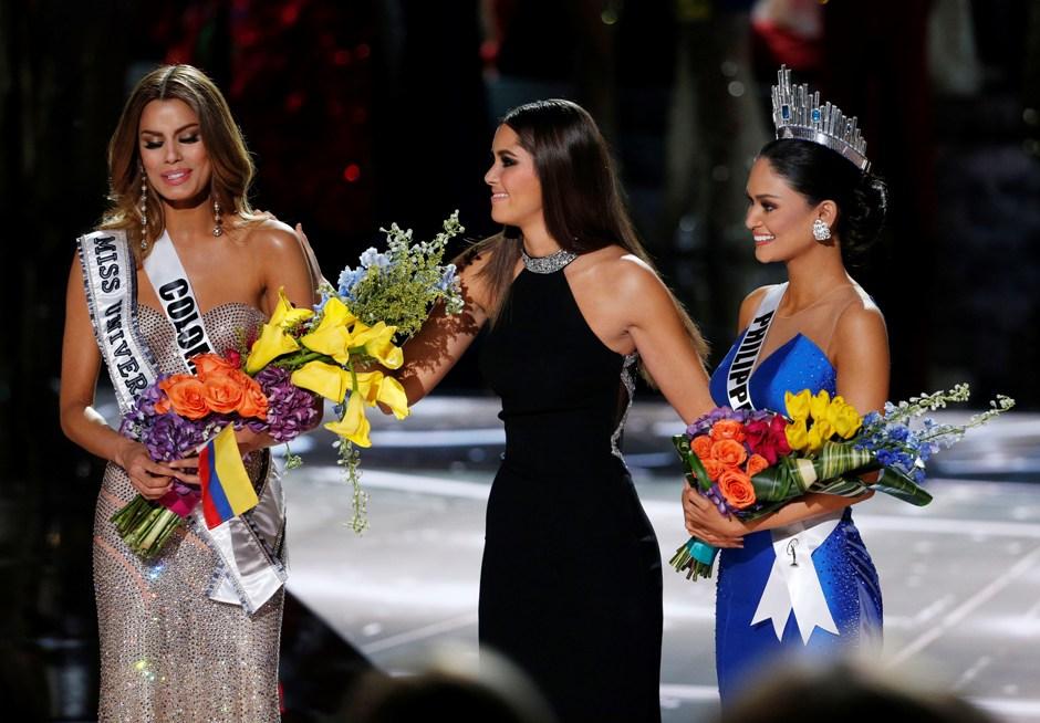 Miss Universo 2014 Paulina Vega, centro, retira la corona y las flores a Miss Colombia Ariadna Gutiérrez, izquierda, antes de entregárselas a Miss Filipinas Pia Alonzo Wurtzbach, derecha, en el concurso Miss Universo el domingo 20 de diciembre de 2015 en Las Vegas.Gutiérrez fue nombrada ganadora por error antes de que Wurtzbach recibiera la corona de Miss Universo. (Foto AP/John Locher)