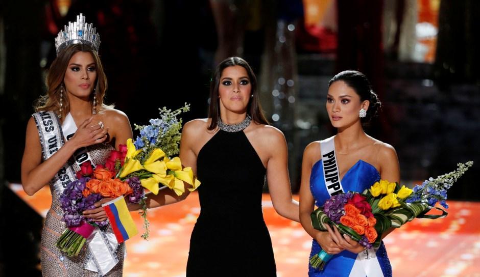 Miss Universo 2014 Paulina Vega, centro, reacciona antes de retirar la corona y las flores a Miss Colombia Ariadna Gutiérrez, izquierda, para entregárselas a Miss Filipinas Pia Alonzo Wurtzbach, derecha, en el concurso Miss Universo el domingo 20 de diciembre de 2015 en Las Vegas. Gutiérrez fue nombrada ganadora por error antes de que Wurtzbach recibiera la corona de Miss Universo. (Foto AP/John Locher)
