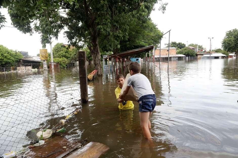 Marino Gomez entrega un saco de comida a su hermano Pablo en una zona inundada del vecindario Bañado Norte, en Asunción, Paraguay, el domingo 27 de diciembre de 2015. Las peores inundaciones de las últimas décadas, causadas por las lluvias, han forzado la evacuación de más de 140.000 personas en Paraguay, Argentina, Uruguay y Brasil. (Foto AP/Jorge Saenz)