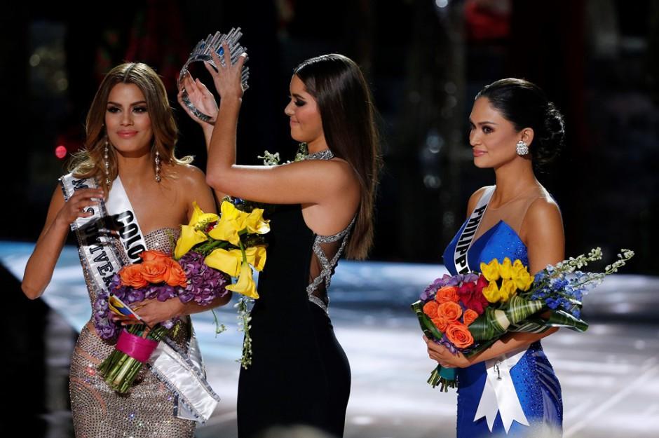 Miss Universo 2014 Paulina Vega, centro, retira la corona a Miss Colombia Ariadna Gutiérrez, izquierda, para entregársela a Miss Filipinas Pia Alonzo Wurtzbach, derecha, en el concurso Miss Universo el domingo 20 de diciembre de 2015 en Las Vegas. Gutiérrez fue nombrada ganadora por error antes de que Wurtzbach recibiera la corona de Miss Universo. (Foto AP/John Locher)