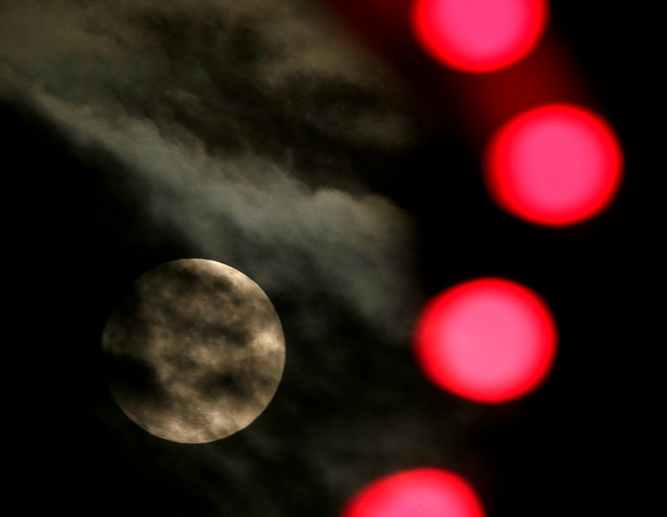 El luna casi llena se ve a través del alumbrado de Navidad en Leneza, Kansas, el jueves 24 de diciembre de 2015. (AP Foto/Charlie Riedel)