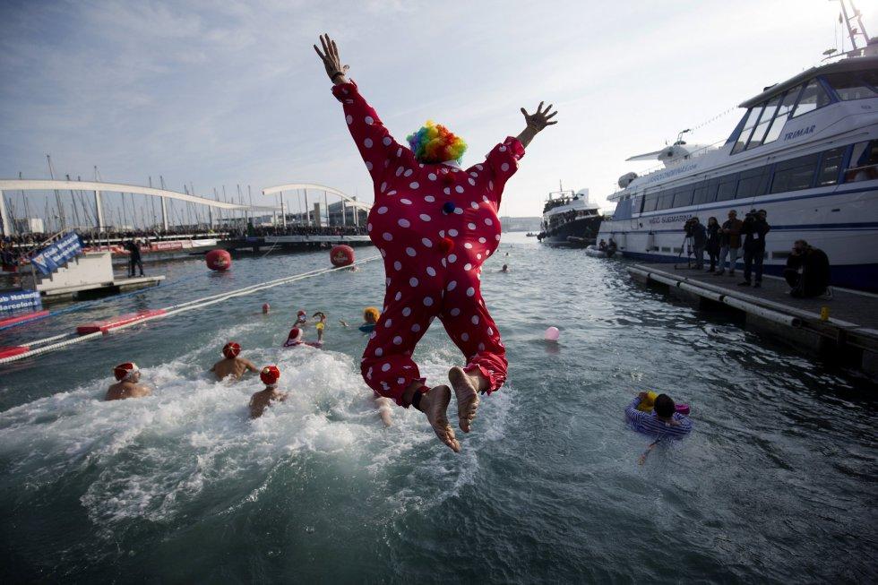 Participantes de todas las edades se lanzan al agua al inicio de la tradicional Copa Nadal, que cumple su edición 106, para celebrar el día de Navidad con una carrera de 200 metros en aguas del puerto de Barcelona. EFE/Alejandro García