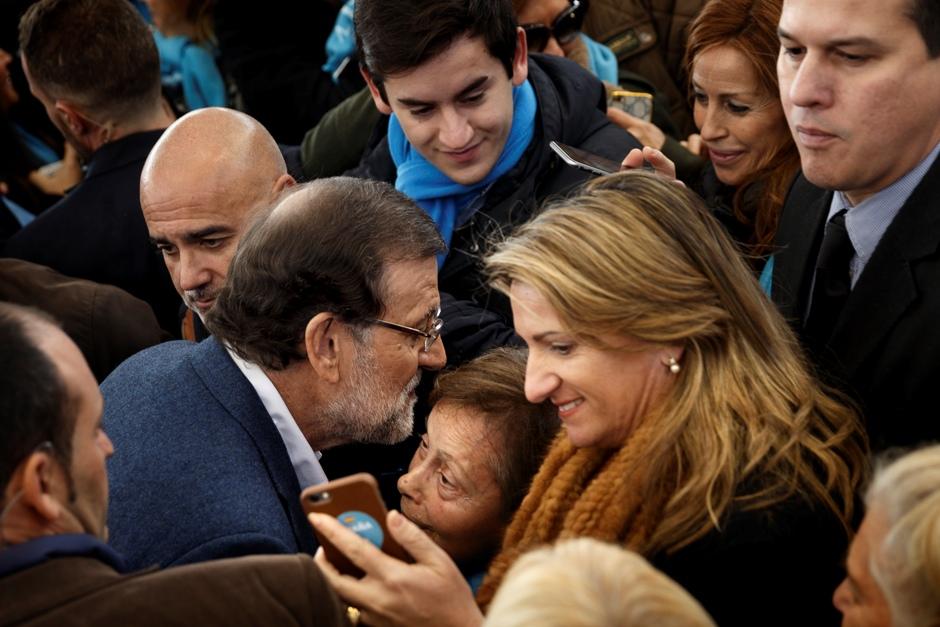 El presidente de gobierno y candidato del Partido Popular español, Mariano Rajoy, besa a una mujer durante un evento de campaña en la Plaza de Toros Las Rozas, cerca de Madrid, el 13 de diciembre del 2015. (Foto AP/Daniel Ochoa de Olza)