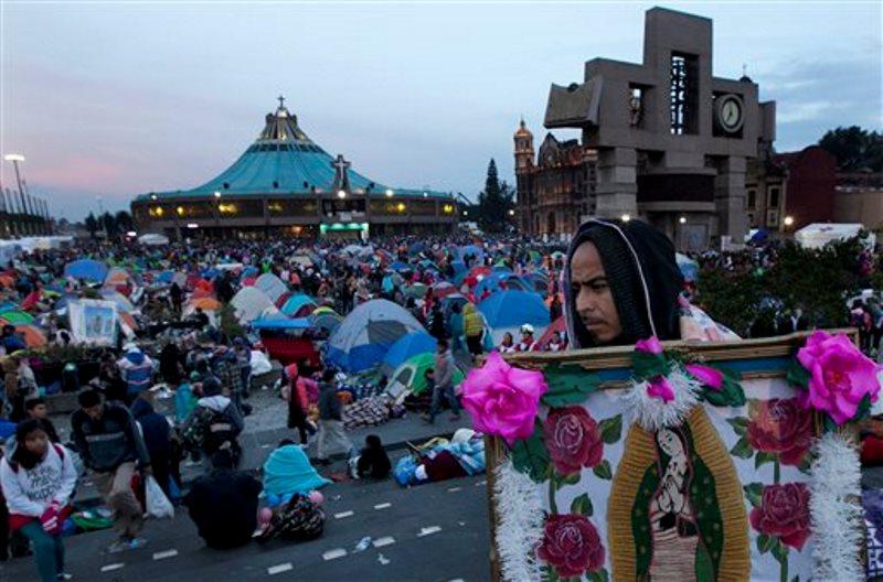 Un hombre carga una imagen de la Virgen de Guadalupe mientras numerosos peregrinos comienzan a despertar el sábado 12 de diciembre después de que pasaran la noche en el atrio de la Basílica de Guadalupe en la ciudad de México. Al fondo se ve la parte superior de la basílica. Miles de peregrinos de diversas partes del país convergen en este templo católico con imágenes o estatuas de la santa patrona de México para que se las bendigan durante la misa por el día de la virgen, el 12 de diciembre. Nuestra Señora de Guadalupe es la imagen religiosa y cultural más popular de México.  (AP Foto/Marco Ugarte)