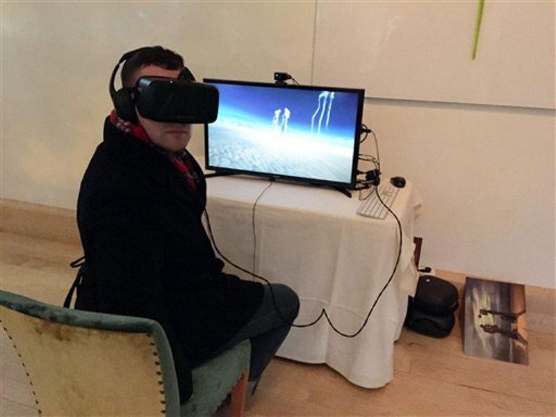 En esta foto del 14 de enero del 2016 el reportero de Skift.com Dan Peltier usa un casco Oculus Rift para probar una experiencia de realidad presentada por el Museo de Dalí en Florida en una presentación a los medios en Nueva York. La experiencia es parte de una muestra sobre la relación del Salvador Dalí con Walt Disney. (AP Foto/Beth J. Harpaz)