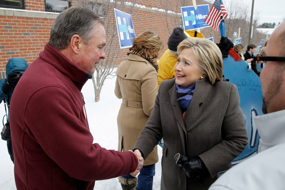 La precandidata presidencial demócrata Hillary Clinton habla con Frank Fiorina, esposo de Carly Fiorina, precandidata presidencial republicana, mientras hacen campaña afuera de una casilla electoral durante las primeras primarias presidenciales en esta campaña en Estados Unidos, el martes 9 de febrero de 2016 en Derry, New Hampshire. (Foto AP/Matt Rourke)