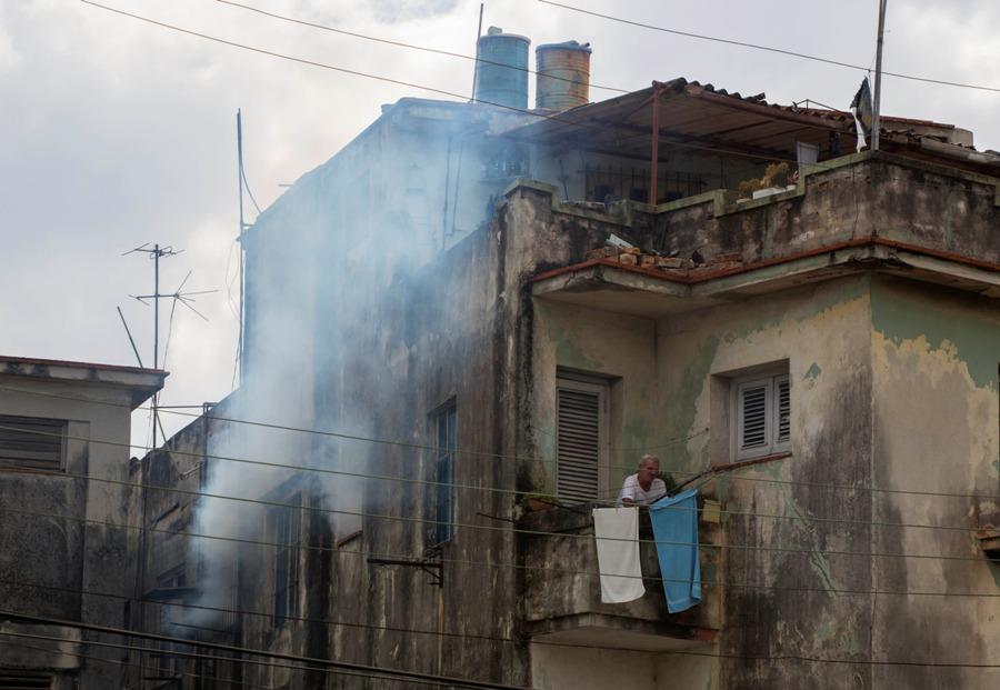 Un hombre espera en el balcón de su casa mientras es fumigada el 22 de febrero del 2016. El gobierno lanzó una campaña destinada a mantener a Cuba como el único país del continente sin el brote del virus del zika. El presidente Raúl Castro dijo que todavía no se ha registrado un solo caso de zika en Cuba. (AP Photo/Desmond Boylan)