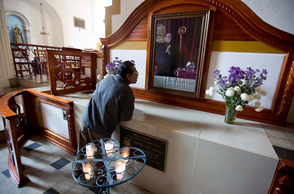 En esta imagen del 17 de enero de 2016, un hombre lee información bajo una foto del fallecido obispo Samuel Ruiz, colocada sobre la tumba de Ruiz en la catedral de San Cristóbal de Las Casas, en el estado sureño mexicano de Chiapas. Ruiz era apreciado por los indígenes y detestado entre las clases acomodadas y parte de la jerarquía eclesiástica. Muchos altos cargos acusaron a Ruiz de actuar en nombre de los rebeldes zapatistas en su alzamiento de 1994 por más derechos indígenas. (AP Foto/Eduardo Verdugo)