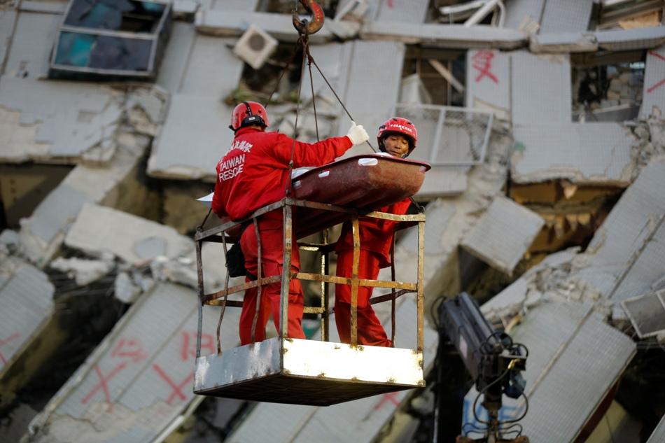 Dos socorristas transportan a una víctima retirada de entre los restos de un edificio de apartamentos en Tainan, Taiwán, el domingo 7 de febrero de 2016. Los socorristas detectaron el domingo señales de vida entre los restos del inmueble que se vino abajo durante un poderoso sismo que dejó el día anterior al menos 32 muertos y centenares de heridos en el sur de Taiwán. (AP Foto/Wally Santana)