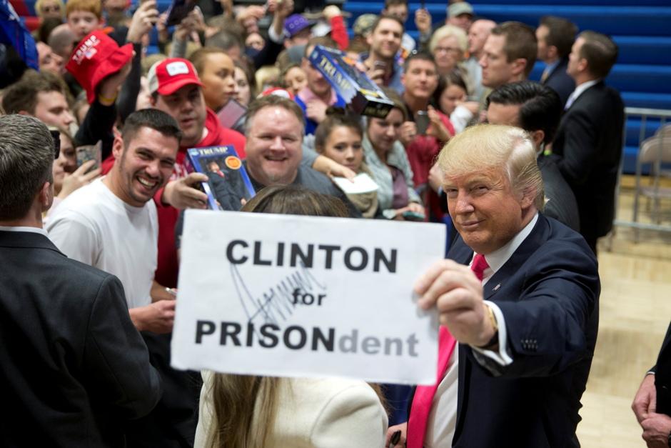 """Donald Trump, aspirante a la candidatura republicana a la presidencia, muestra un cartel con su autógrafo que incluye un juego de palabras sobre la precandidata demócrata Hillary Clinton, confundiendo """"presidenta"""" y """"prisión"""", durante un acto electoral el domingo 31 de enero de 2016, en Council Bluffs, Iowa. (AP Foto/Jae C. Hong)"""