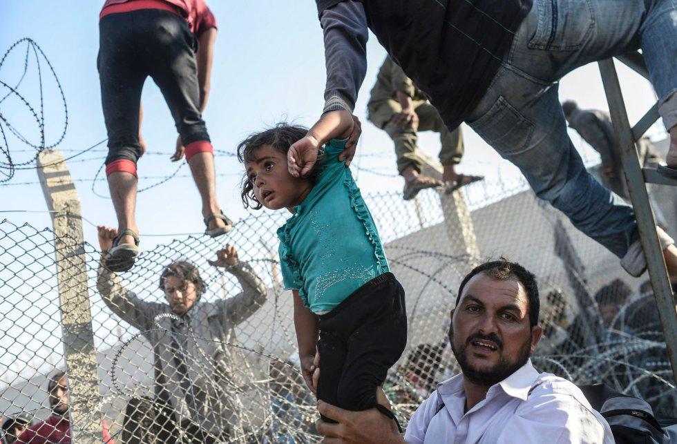 Los asilados entran en Turquia tras romper la valla que le separa de Siria. Es el tercer premio en el apartado de historias TERCER PREMIO EN HISTORIAS DE NOTICIAS DE ACTUALIDAD. BULENT KILIC (AFP)