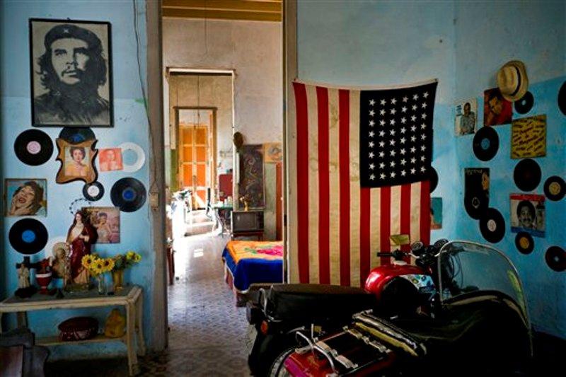 """Una foto del revolucionario Ernesto """"Che"""" Guevara está en una pared y en la otra  hay bandera de EEUU en una vivienda en La Habana, Cuba, el martes 15 de marzo de 2016. Cinco días antes de que se realice el primer viaje de un presidente de EEUU a La Habana en casi 90 años, el gobierno de Barack Obama le propinó una serie de golpes al embargo comercial a Cuba al convertir la prohibición de viajar a la isla en un sistema que depende de que las personas digan que el propósito de que su viaje es educativo, y no turístico, y al allanar el camino para que jugadores de béisbol, y otros atletas profesionales, puedan algún día jugar en las Grandes Ligas o en otras ligas profesionales estadounidenses. (Foto AP / Ramón Espinosa)"""