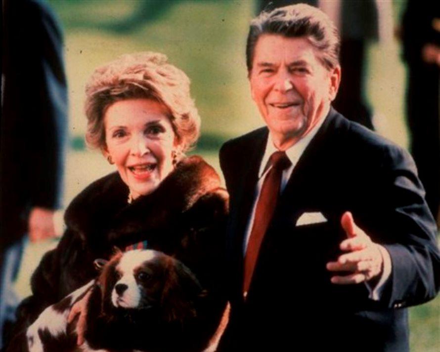 En esta imagen de archivo, tomada en diciembre de 1986, la primera dama de Estados Unidos Nancy Reagan sostiene a la mascota de la familia, Rex, mientras camina junto a su esposo Reagan por el jardín sur de la Casa Blanca. (Foto AP/Dennis Cook, archivo)