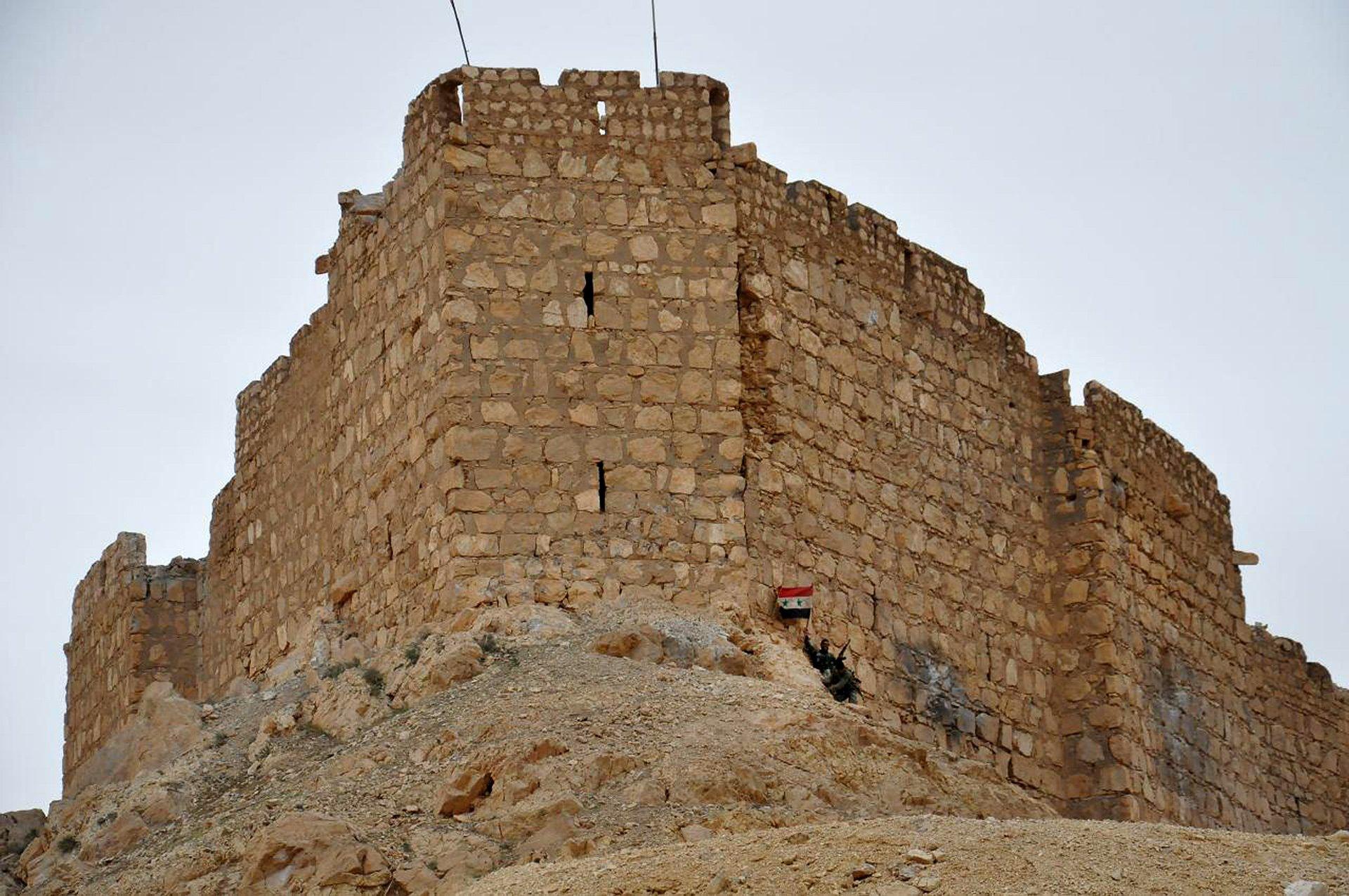 Un soldado sirio celebra con su bandera a los pies de uno de los edificios que sobrevivió a la batalla - Crédito: AP