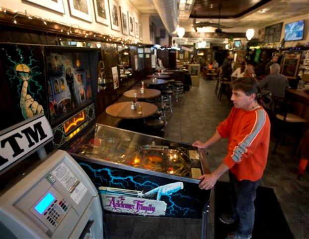 Pat McBride juega pinball en el McGreary's Irish Pub de Albany, estado de Nueva York, el 4 de febrero del 2016. Bares de barrio como este tienden a desaparecer en Estados Unidos debido a los crecientes costos y la competencia de bares más grandes, llenos de pantallas de televisión. De todos modos, siguen ofreciendo un toque barrial, comunitario, que no pueden reproducir los bares más grandes y que  les permite albergar esperanzas de que muchos sobrevivirán. (AP Photo/Mike Groll)