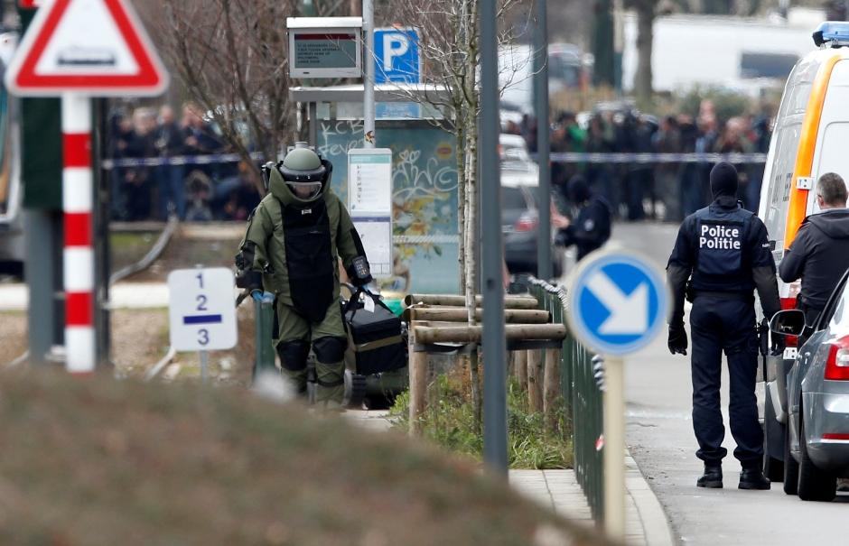 Un socorrista con ropa protectora investiga la escena en Schaerbeek, Bélgica, viernes 25 de marzo de 2016. Un testigo dijo a la emisora estatal belga RTBF que escuchó dos explosiones y ráfagas de armas pesadas cuando la policía realizaba un gran allanamiento en el barrio de Bruselas. (AP Foto/Alastair Grant)