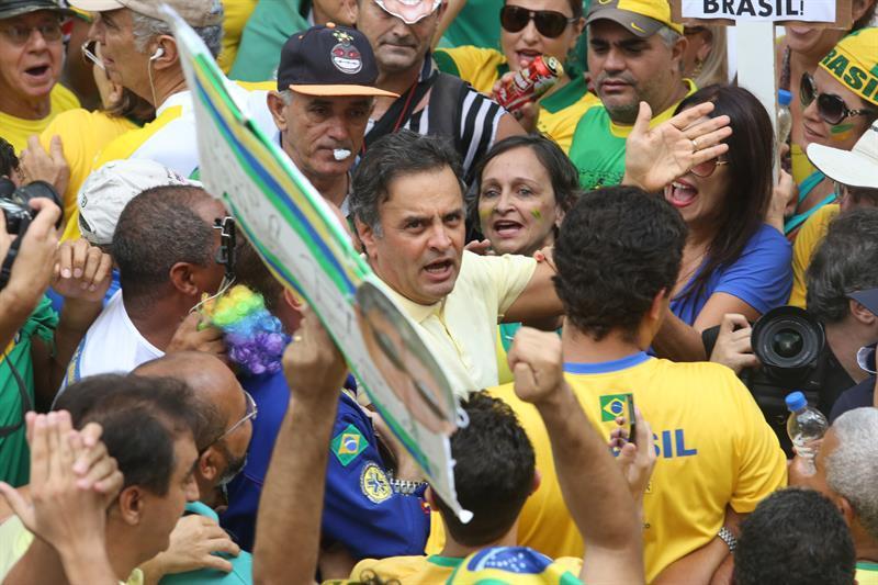 El senador brasileño Aécio Neves (c) participa junto a cientos de manifestantes que se reúnen en la Plaza de la Libertad hoy, domingo 13 de marzo de 2016, para pedir la destitución de la presidenta brasileña Dilma Rousseff en Belo Horizonte, Minas Gerais (Brasil).